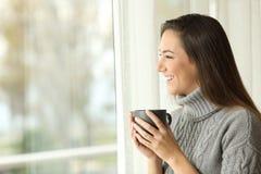 看外面通过窗口的妇女饮用的咖啡 免版税库存照片