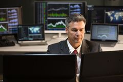 看多个屏幕的股市经纪 免版税库存照片