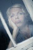 看多雨天气的乏味妇女由窗口 库存照片