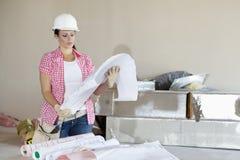 年轻看大厦计划的建筑师佩带的安全帽 免版税库存图片
