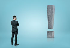看大3D具体惊叹号的后面观点的商人隔绝在蓝色背景 免版税库存照片