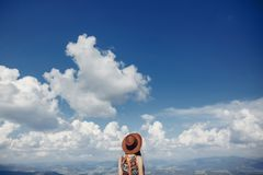 看天空和山的帽子的时髦的旅客妇女 臀部 免版税库存图片