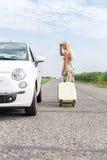 看失败的汽车的妇女,当拉扯在乡下公路时的行李 免版税库存照片