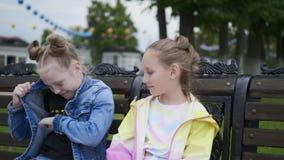 看夹克口袋他们中的一个的长凳的两个青少年的女朋友 股票视频