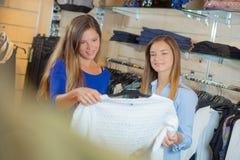 看套头衫的两个女朋友在商店 库存图片