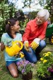 看女孩浇灌的花的快乐的资深妇女 免版税库存照片