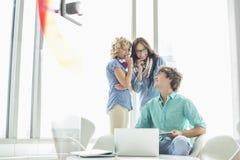 看女性同事的微笑的商人说闲话在创造性的办公室 免版税图库摄影