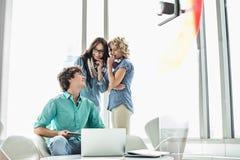 看女性同事的微笑的商人说闲话在创造性的办公室 免版税库存照片