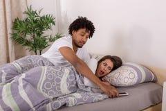 看女朋友的嫉妒的男朋友在卧室打电话 库存图片