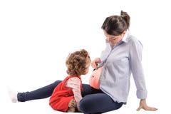 看她在白色的被隔绝的第一个孩子怀孕的母亲腹部 免版税库存照片