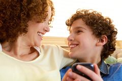 看她微笑的儿子的愉快的母亲 免版税库存照片