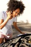 看她残破的汽车和打电话的非洲妇女为协助 免版税图库摄影