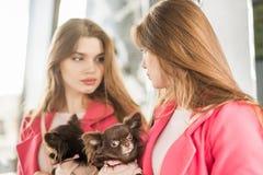 看她的在镜子的桃红色外套的女孩反射 免版税库存照片