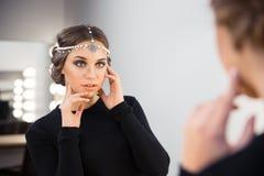 看她的在镜子的迷人的妇女反射 免版税库存照片