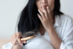 看她的头发的妇女为掉头发问题 免版税库存照片