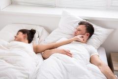 看她的妻子的人睡觉在床上 免版税库存照片