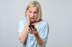 看她的手机的惊奇的妇女 免版税库存图片