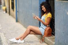 看她的数字式片剂的年轻阿拉伯妇女户外 免版税库存照片