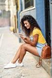 看她的数字式片剂的年轻阿拉伯妇女户外 免版税图库摄影