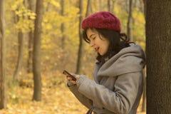 看她的智能手机的俏丽的女孩在森林 库存照片