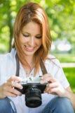 看她的照相机的俏丽的红头发人在公园 免版税图库摄影