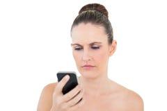 看她的电话的恼怒的妇女 免版税库存照片
