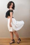 看她的白色裙子的美丽的年轻深色的妇女 图库摄影