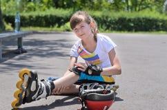 看她的被挫伤的胳膊的四轮溜冰者 库存照片