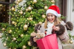 看她的驯鹿圣诞节礼物的愉快的女孩 库存图片