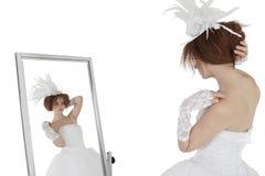 看她自己的婚礼服的年轻深色的新娘在白色背景的镜子 免版税图库摄影