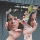 看她自己的美丽的女孩在一个残破的镜子 图库摄影