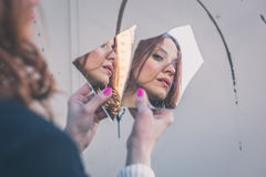 看她自己的美丽的女孩在镜子 免版税图库摄影