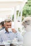 看妇女的中年人,当喝咖啡在边路咖啡馆时 免版税库存照片