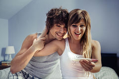 看妊娠试验的年轻夫妇在卧室 免版税库存照片