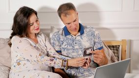 看婴孩扫描的愉快的夫妇 免版税库存图片