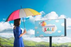 看季风在广告牌的愉快的亚裔妇女销售标志 免版税库存图片
