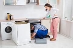 看安装工的妇女修理洗碗机 免版税库存照片