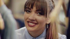 看对与微笑的照相机的一名成人快乐的妇女的接近的射击在一个机架的衣裳之间在服装店 股票录像