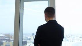 看对从窗口的冬天城市的后面看法商人在营业所 影视素材