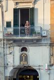 看对从阳台的街道的更老的地方妇女在波利尼亚诺阿马雷,意大利 免版税库存图片