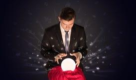 看对在一个不可思议的球和乱画概念的启发的商人 免版税图库摄影