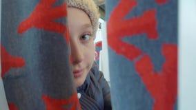 看对在乘客座位之间的照相机的哀伤的女孩少年在城市公共汽车上 在位子的年轻少年女孩就座在地铁 股票视频