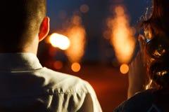 看对在天空的烟花的浪漫夫妇 免版税库存图片
