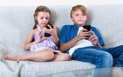 看对在沙发的智能手机的两个孩子 免版税库存照片