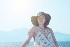 看对在贴水帕帕佐普洛斯口岸的照相机的年轻俏丽的妇女室外夏天画象,享用她的自由和新鲜空气 库存照片