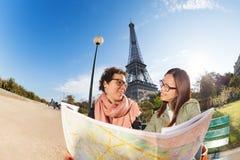 看对地图的两个朋友在艾菲尔铁塔附近 免版税图库摄影