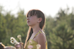 看对天空的梦想的青少年的女孩夏天草甸 免版税库存照片