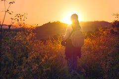 看对太阳的妇女背包徒步旅行者 免版税库存图片