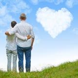 看对心脏的老夫妇在天空覆盖 免版税库存图片