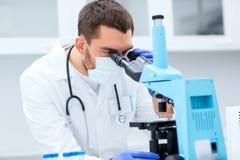 看对显微镜的年轻科学家在实验室 免版税图库摄影